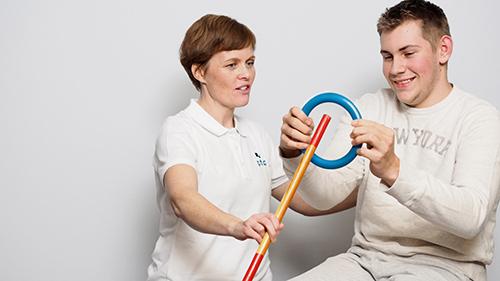 fotografi for nedlasting - smilende dame og mann trener med ring og trepinne