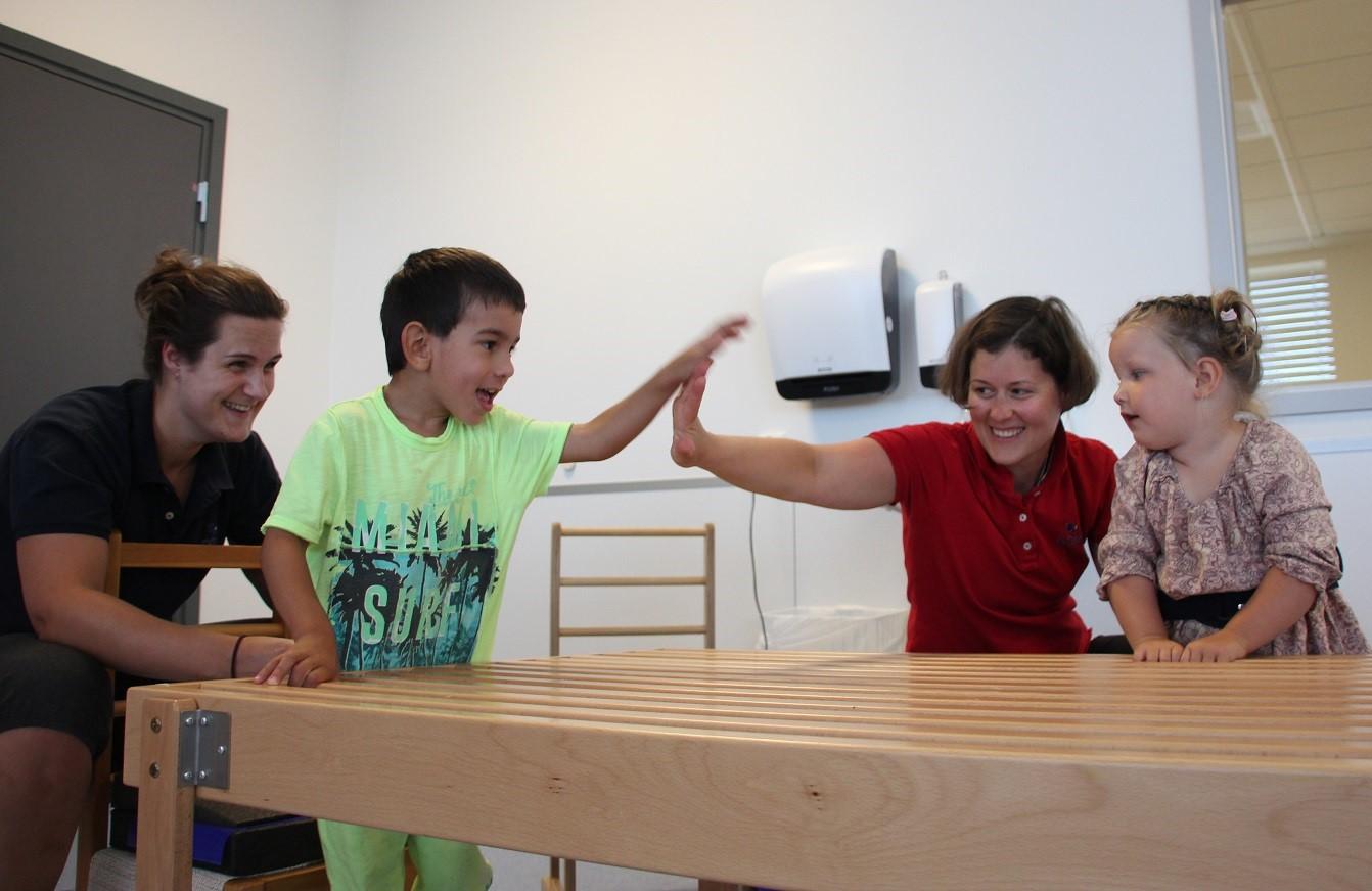Bilde av ergoterapeut Anette Sjøstrøm, Millian, habiliteringspedagog Zsuzsanna Fenyő og Olivia.