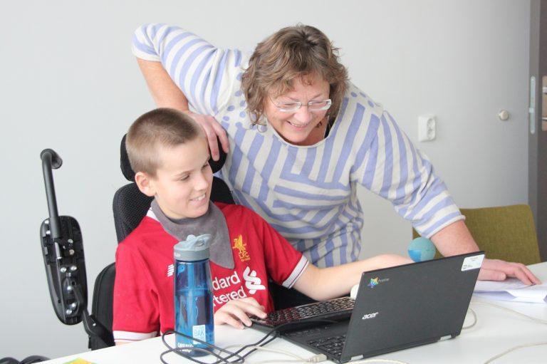 Bilde av Eirik Sander Viken og lærer Arnhild Eliassen som jobber med skolearbeidet sammen.