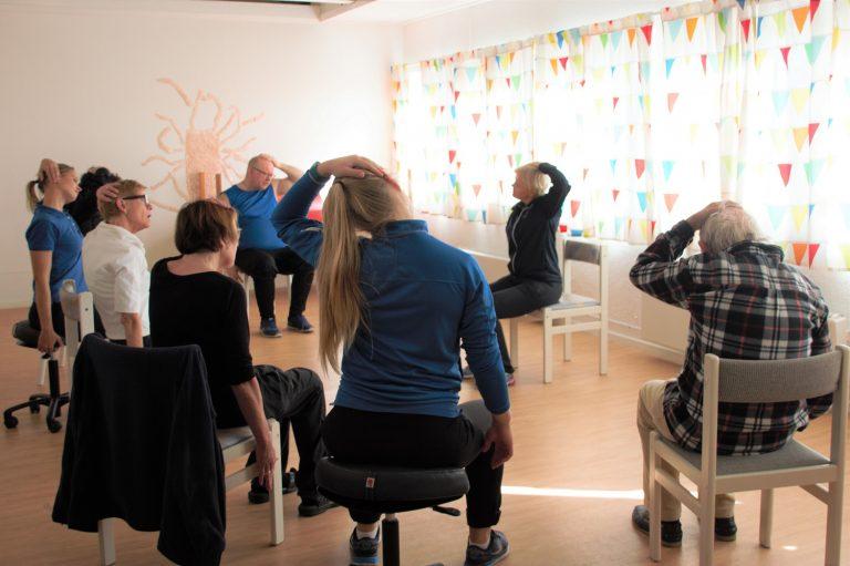 Bilde av Parkinsongruppa ved PTØ Stavanger som sitter i en ring med en hånd på eget hode.