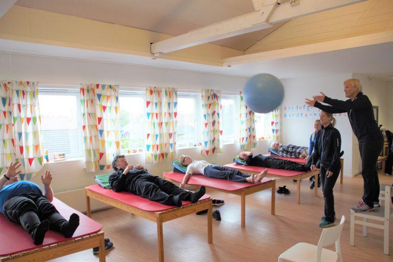 Bilde av Parkinsongruppa som ligger på hver sin benk mens Kari Hapnes kaster en overraskende ball ut i rommet.