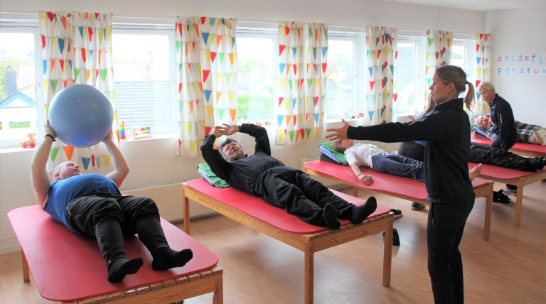 Bilde av habiliteringspedagog Ingvild Frøysang som kaster en ball til deltakerne i Parkinsongruppa.