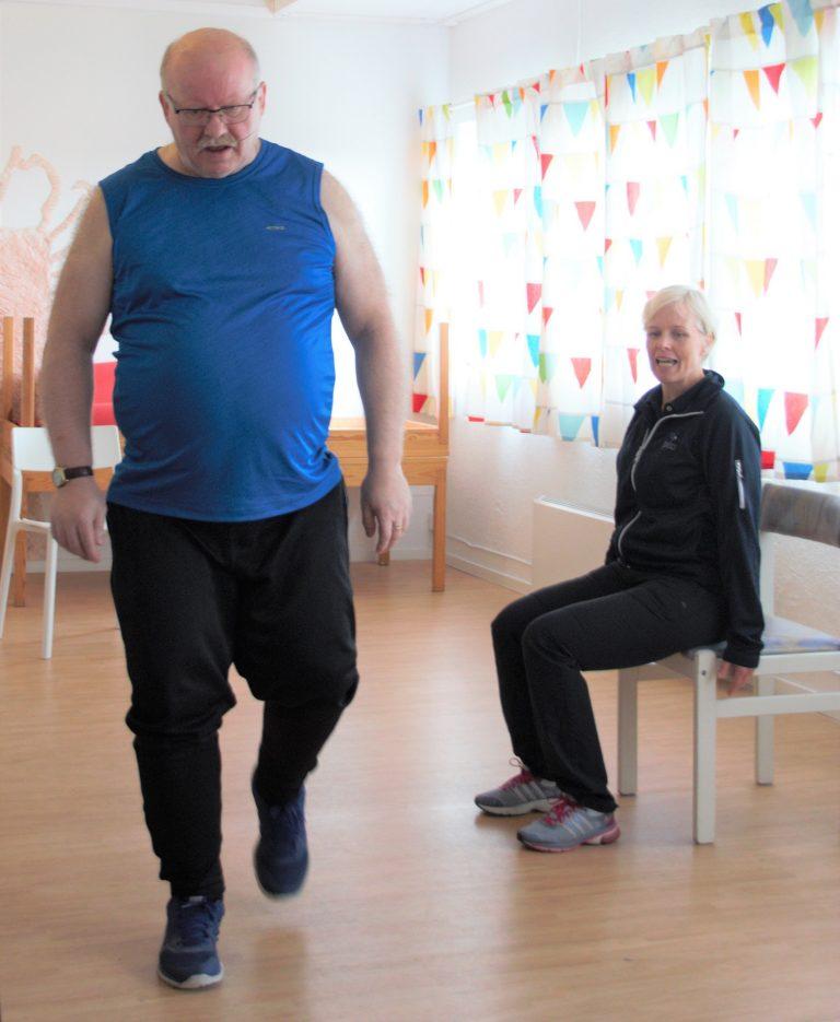 Bilde av Ingvar Josdal som går i treningsrommet mens Kari Hapnes hjelper ham med rytmen.
