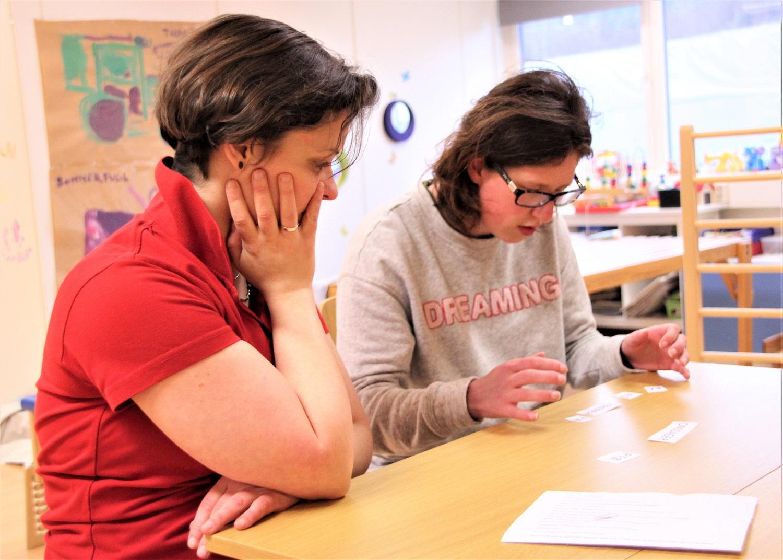 Bilde av habiliteringspedagog Zsuzsanna Fenyő og Kristin Nerdal som setter sammen papirlapper med ord.