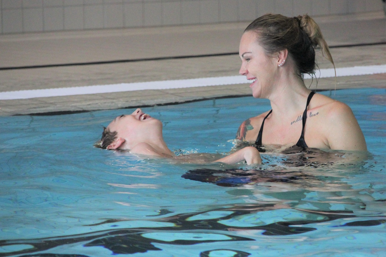 Bilde av gutt i bassenget med sin mor.