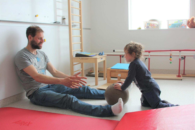 Henrik skyver en ball langs gulvet bort til faren sin.