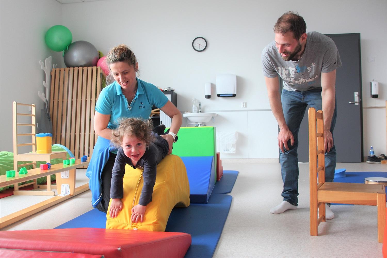 Bilde av Henrik (2) som trener sammen med habiliteringspedagog Barbara. Pappa Kristoffer er også til stede.