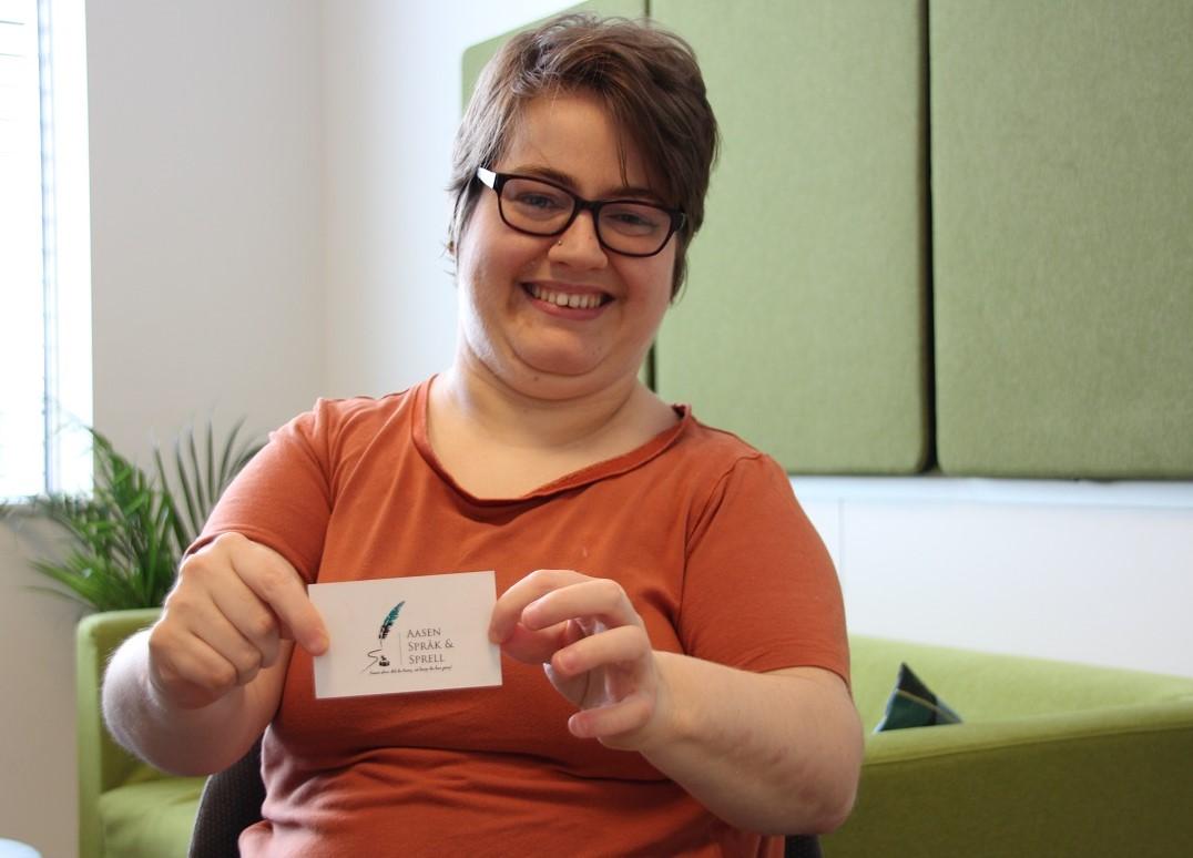 Bilde av Merete Aasen som viser fram visittkortet til firmaet sitt.